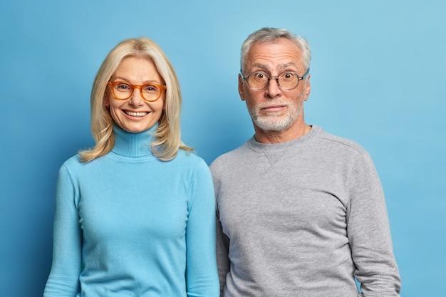 Retrato de um homem barbudo surpreso e uma mulher loira de meia-idade feliz, próximos um do outro, usando macacões casuais isolados sobre a parede azul do estúdio