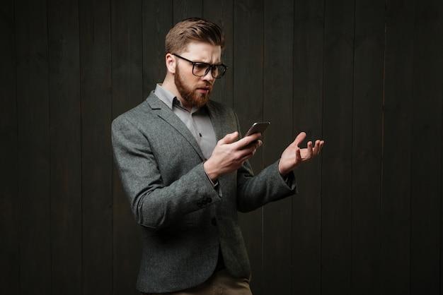 Retrato de um homem barbudo surpreso em óculos e terno casual, segurando o telefone móvel isolado no fundo preto de madeira