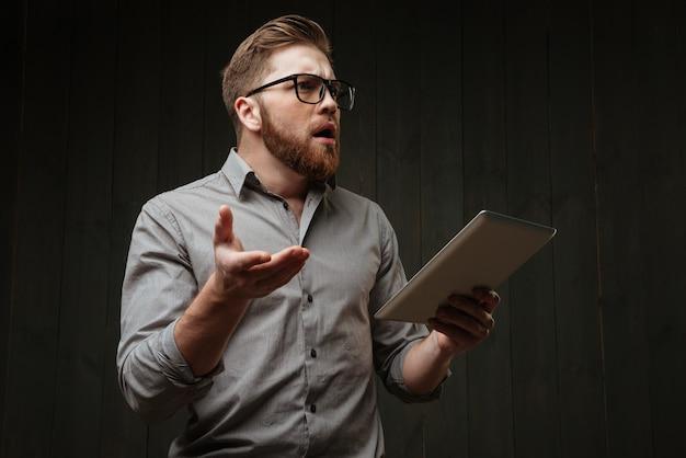 Retrato de um homem barbudo surpreso em óculos segurando um computador tablet e gesticulando isolado em uma superfície de madeira preta