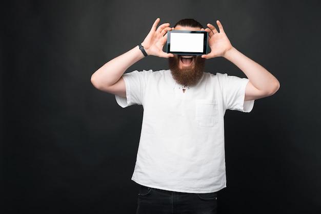 Retrato de um homem barbudo surpreso segurando um tablet sobre os olhos com uma tela branca