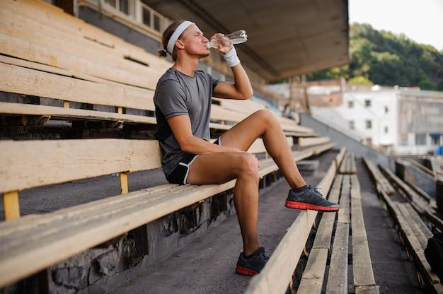 Retrato de um homem beber água de garrafa
