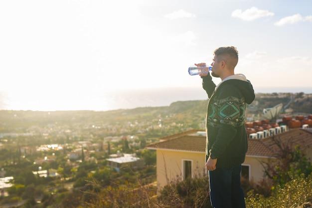 Retrato de um homem beber água de uma garrafa fora