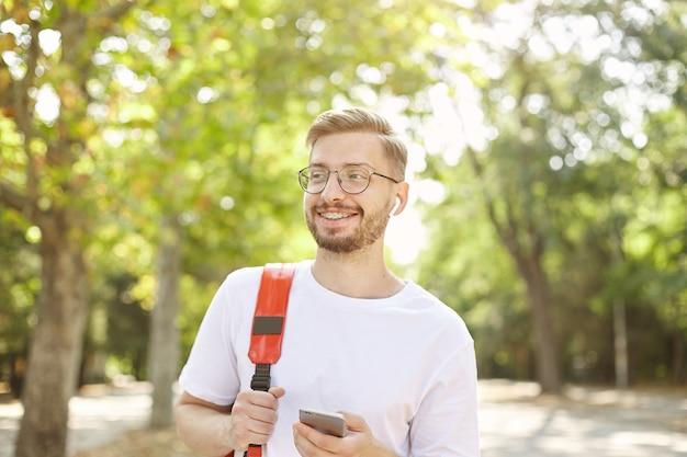 Retrato de um homem bem parecido e feliz com o celular na mão, olhando para longe e sorrindo amplamente, vestindo camiseta branca e mochila vermelha, caminhando pelo parque em um dia claro e quente
