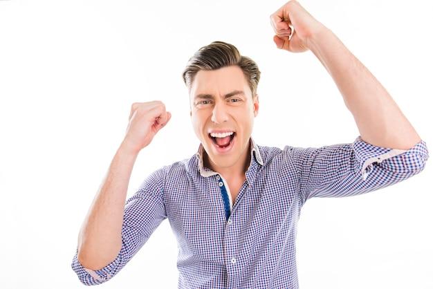 Retrato de um homem bem-sucedido e feliz alcançando seu objetivo com as mãos levantadas