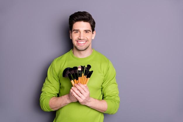 Retrato de um homem bem-sucedido, visagiste positivo, segurando escovas para fazer maquillage para sessão de fotos de eventos noturnos especiais, usar um suéter verde isolado sobre a parede cinza