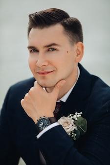 Retrato de um homem bonito, caucasiano, com cabelo curto e escuro, olha para a câmera e sorri