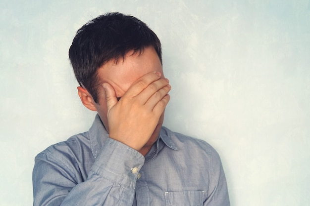 Retrato de um homem bonito, cobrindo os olhos com as mãos isoladas em um fundo branco, um jovem de camisa azul está segurando sua cabeça. o conceito de fadiga. feche os olhos para o problema.