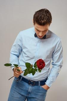 Retrato de um homem bonito com uma rosa vermelha como um presente em suas mãos
