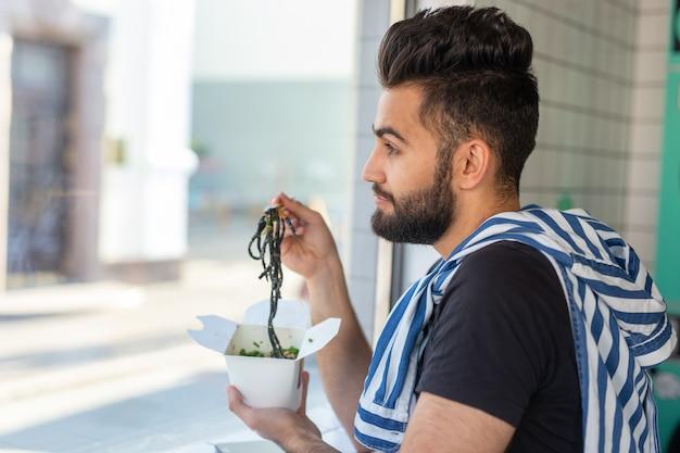 Retrato de um homem bonito comendo macarrão chinês em um café e olhando pela janela. o conceito de cozinha asiática saudável.