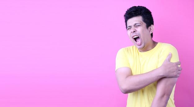 Retrato de um homem bonito da ásia, segurando seu ombro com dor no fundo rosa no estúdio