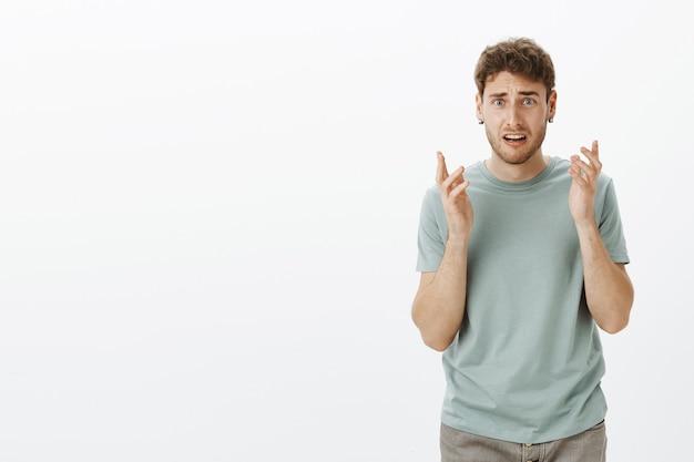Retrato de um homem bonito descontente em estado de choque com cabelo loiro em uma camiseta da moda, gesticulando com expressão confusa, carrancudo