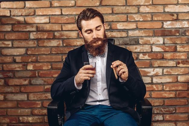 Retrato de um homem bonito e atraente com bigode e barba, sentado em uma cadeira e segurando um copo de uísque e um charuto na mão, posando contra uma parede de tijolos. conceito de sharm masculino