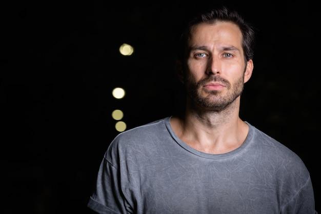 Retrato de um homem bonito e barbudo escandinavo na rua à noite