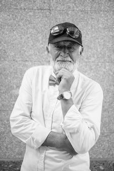 Retrato de um homem bonito e barbudo turista sênior vestindo roupas elegantes enquanto explora a cidade de bangkok em preto e branco