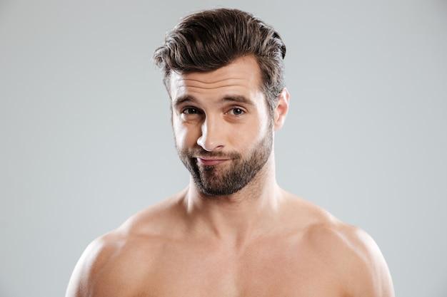 Retrato de um homem bonito e duvidoso com ombros nus