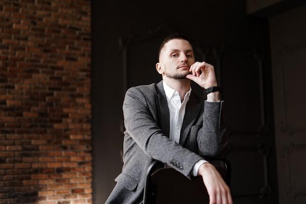 Retrato de um homem bonito e elegante de camisa branca sentado em uma cadeira em um estúdio fotográfico