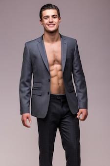 Retrato de um homem bonito e sexy com uma jaqueta e um torso nu isolado em uma parede branca