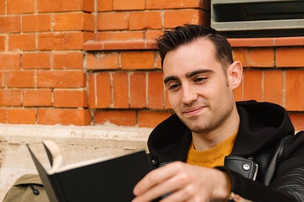 Retrato de um homem bonito e sorridente com traços hispânicos e latinos, enquanto lê um livro ao ar livre. conceito de estilo de vida de rua.