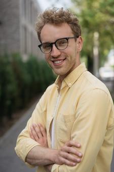 Retrato de um homem bonito e sorridente, vestindo uma camisa casual e óculos elegantes, olhando para a câmera