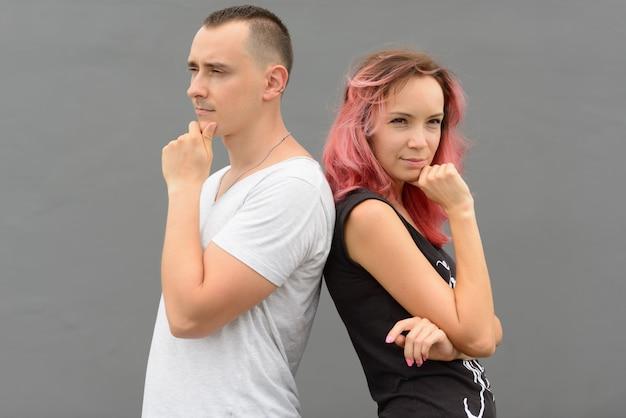Retrato de um homem bonito e uma linda mulher com cabelo rosa como casal juntos e apaixonados contra uma parede cinza ao ar livre