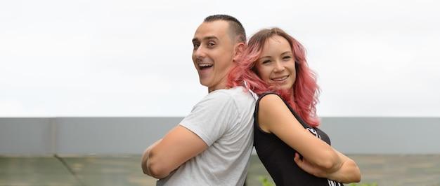 Retrato de um homem bonito e uma linda mulher com cabelo rosa como casal juntos e apaixonados no parque ao ar livre