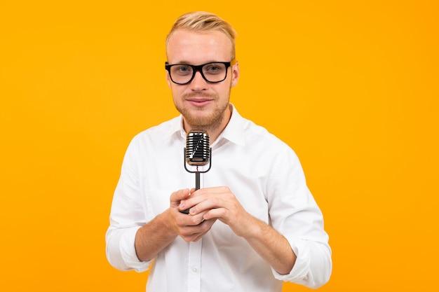 Retrato de um homem bonito em uma camisa branca com um microfone retrô cantando em uma parede amarela