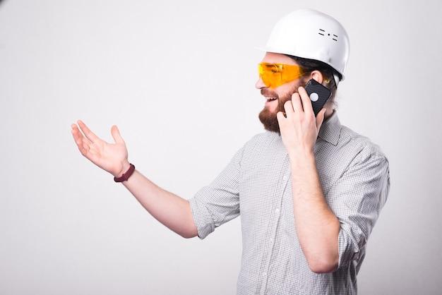 Retrato de um homem bonito engenheiro falando no telefone, gesticulando e usando um capacete branco