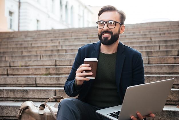 Retrato de um homem bonito feliz em óculos