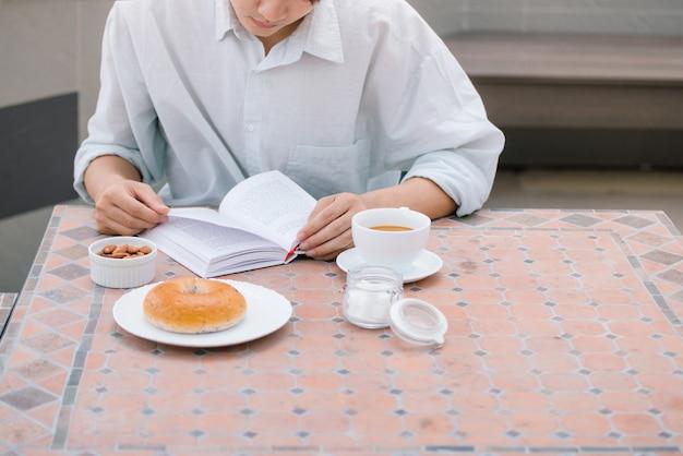 Retrato de um homem bonito, lendo um livro e apreciando seu café.