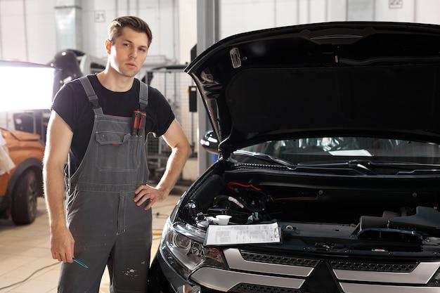 Retrato de um homem bonito mecânico de automóveis em pé perto do capô do carro na oficina de automóveis