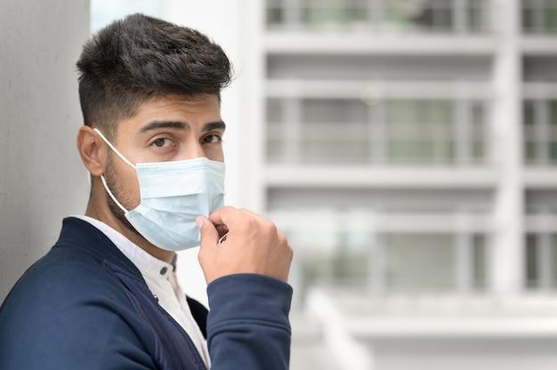 Retrato de um homem bonito na máscara médica, olhando para a câmera na cidade jovem bonito, destacando-se ...