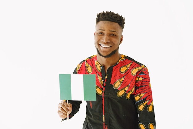 Retrato de um homem bonito nigeriano vestido em trajes tradicionais igbo. ele está carregando a bandeira da nigéria.