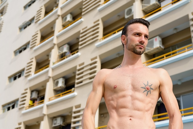Retrato de um homem bonito sem camisa ao ar livre com tanques abdominais e tatuagens