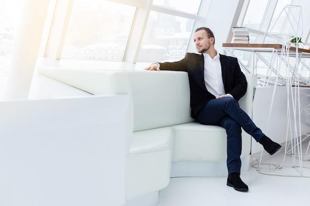 Retrato de um homem bonito, sentado no sofá no interior moderno branco.