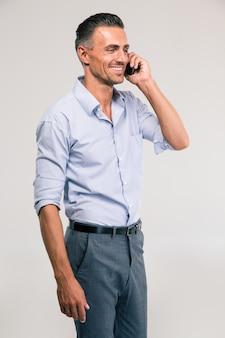 Retrato de um homem bonito sorridente falando ao telefone e desviando o olhar isolado