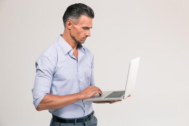 Retrato de um homem bonito usando laptop isolado