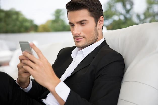Retrato de um homem bonito usando smartphone ao ar livre em restaurante