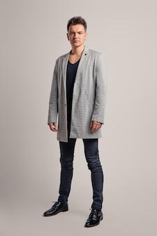 Retrato de um homem bonito, vestindo jaqueta de lã, camisa preta e calça jeans