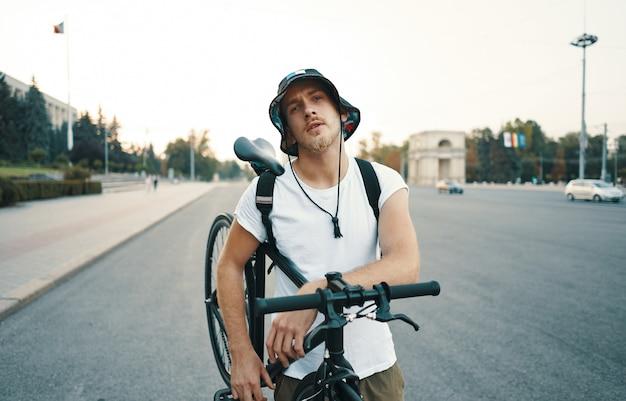Retrato de um homem branco loiro na cidade com uma bicicleta clássica