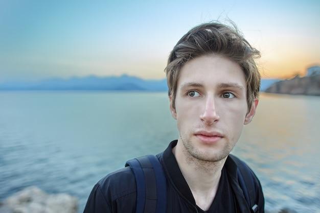 Retrato de um homem branco triste com traços delicados tendo como pano de fundo o pôr do sol no mar