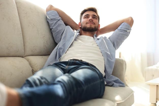 Retrato de um homem cansado casual, descansando sentado em um sofá em casa.