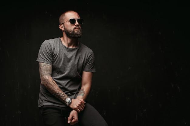 Retrato de um homem careca bonito com barba longa e bem aparada, usando óculos escuros e camisa cinza, olhando para o lado