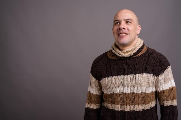 Retrato de um homem careca bonito contra um fundo cinza