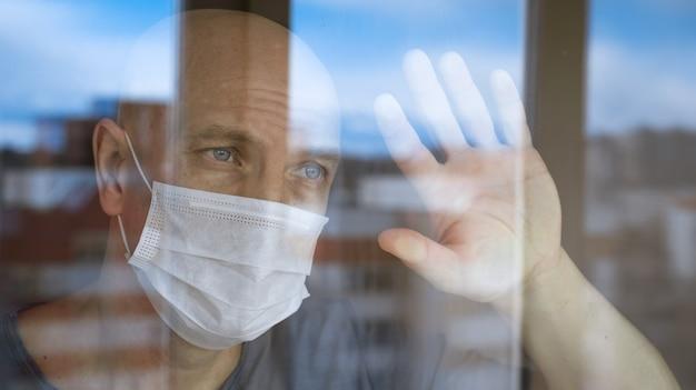Retrato de um homem careca com uma máscara protetora olhando pela janela