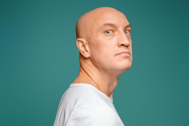 Retrato de um homem careca em uma camiseta branca, expressão facial