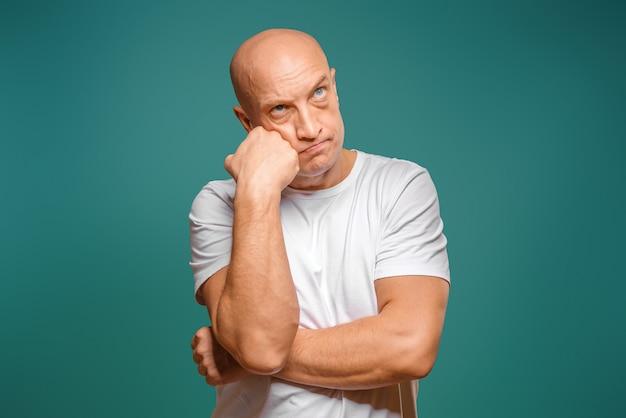 Retrato de um homem careca em uma camiseta branca na expressão pensativa, segurando um dedo perto de seu templo