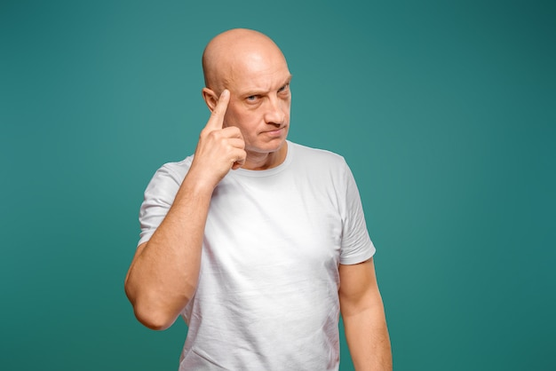 Retrato de um homem careca emocional em uma camiseta branca sobre um fundo azul.
