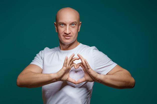 Retrato de um homem careca, sorrindo e de mãos dadas em forma de coração, numa superfície azul