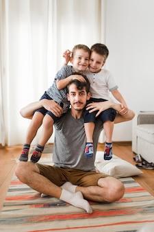 Retrato, de, um, homem, carregar, seu, dois filhos, ligado, ombro, casa