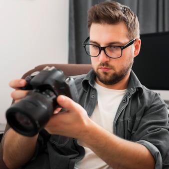 Retrato de um homem casual conferindo uma câmera profissional